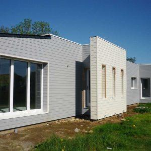 Maison passive en bois avec un habillage gris et blanc